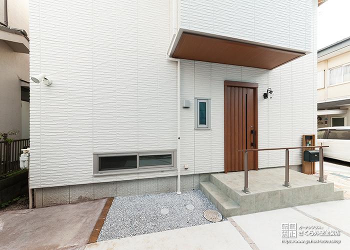 木調の玄関ドアと白い外壁